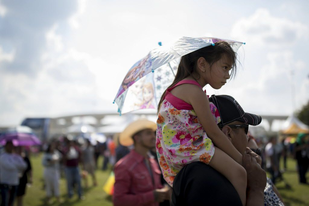 Jose Palomo, of Gainesville, Texas carries his granddaughter J.J., 4, on his shoulder watching the performance on stage during La Grande 107.5 Fiestas Patrias at Reunion Park on Sept. 4, 2016 in Dallas.