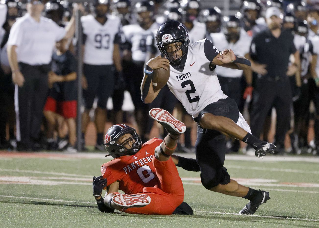 Euless Trinity quarterback Ollie Gordon (2) runs for yardage as he is defended by Colleyville Heritage player Dylahn McKinney (8) during the first half of a high school football game in Grapevine, Texas on Friday, Sept. 10, 2021. (Michael Ainsworth/Special Contributor)