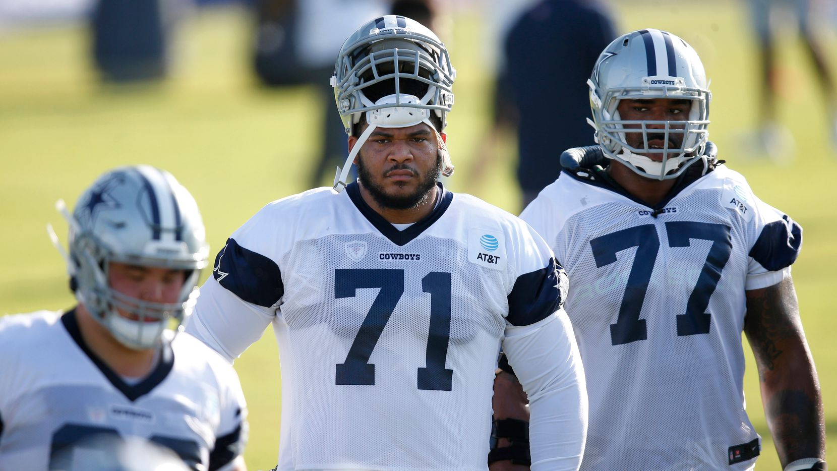 Cowboys offensive tackles La'el Collins (71) and Tyron Smith (77) watch a drill in progress during the first day of training camp at The Star in Frisco on Friday, Aug. 14, 2020.