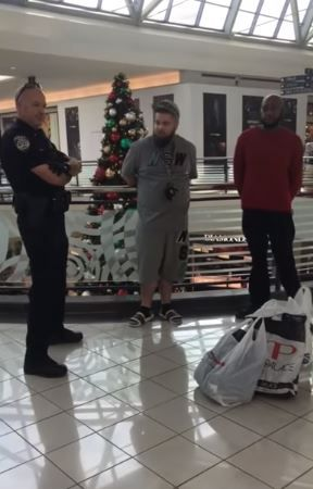 Brandon Kibart (center) and Ro Lockett (right) talk with a Frisco police officer after they were handcuffed and accused of shoplifting at Stonebriar Mall on Wednesday, Nov. 21, 2018.