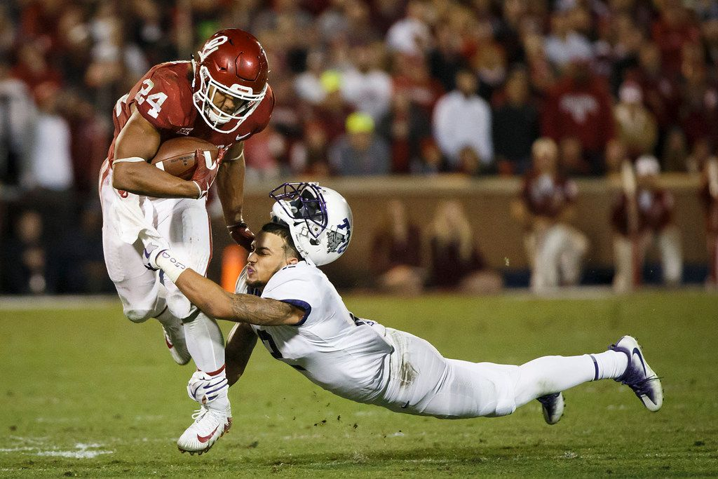 TCU safety Niko Small (2) has his helmet knocked off as he tries to bring down Oklahoma running back Rodney Anderson (24) during the second half of an NCAA football game in Norman, Okla., Saturday, Nov. 11, 2017. (Smiley N. Pool/The Dallas Morning News)