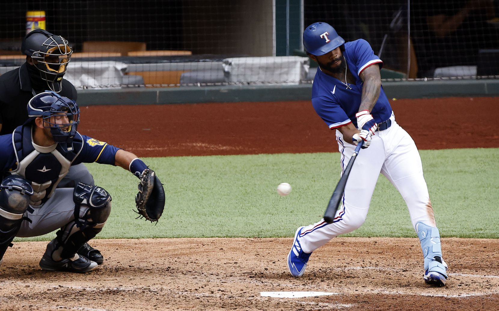 Texas Rangers batter Delino DeShields swings and misses, striking out against the Milwaukee Brewers to end the seventh inning at Globe Life Field in Arlington, Texas. The teams were playing in an exhibition game, Tuesday, March 30, 2021. (Tom Fox/The Dallas Morning News)