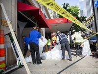 Crews worked to clean up the Neiman Marcus storefront on Main Street on Saturday after it was damaged in the protests.