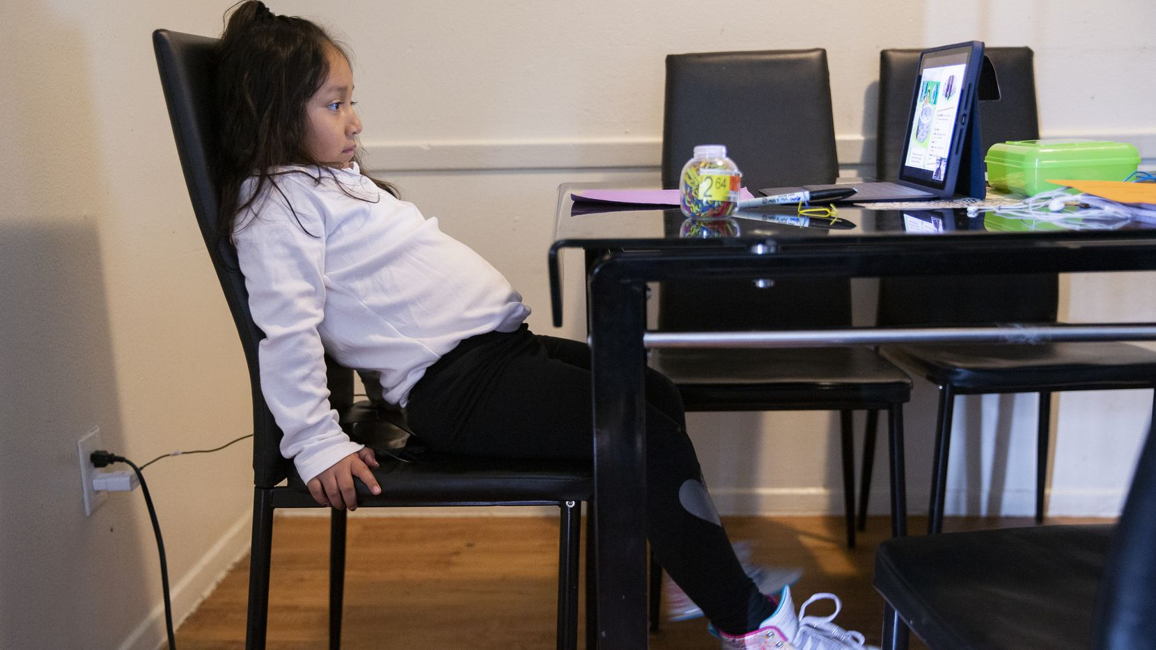 Daysha Cojulum, 5, grew restless while attending virtual school at her kitchen table in northwest Dallas on Sept. 16, 2020. She used her mother's phone to connect to the internet due to the DISD hotspots not working properly or running out of the allotted data.
