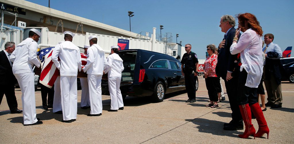A Navy honor guard places remains of Seaman 1st Class George A. Coke Jr., of Arlington, into a hearse after they were unloaded from a commercial flight at Dallas-Fort Worth International Airport, Friday, June 23, 2017, Grapevine, Texas. Coke, who perished aboard the USS Oklahoma after it sank at Pearl Harbor, was identified through recent DNA testing. A service for Coke will be held at First United Methodist Church in central Arlington Saturday before being buried at Parkdale Cemetery.