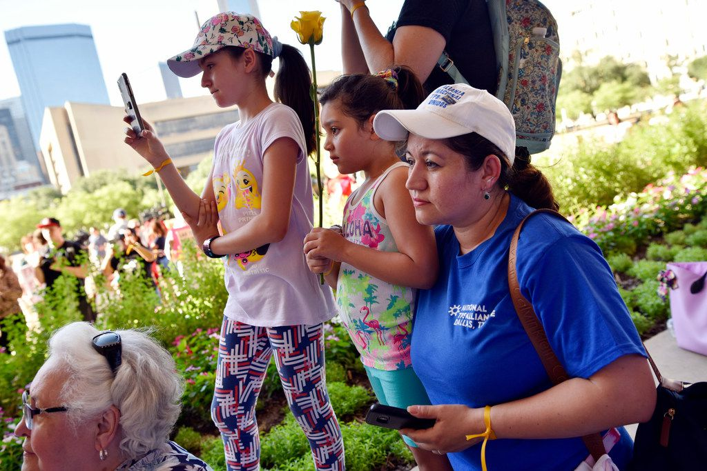 Mili Rivas, far-right, originally of El Salvador, holds her youngest daughter Ariele Rivas, 5, as her sister Suri Rivas, 11, uses her phone to record speakers during a protest of what they say is the cruel and inhumane treatment of immigrants in the U.S., Thursday evening outside of City Hall in Dallas, June 14, 2018. The rose Ariele is holding represents a child who has been separated from family. The protest was conducted by local activists and the organization Families Belong Together. (Ben Torres/Special Contributor)