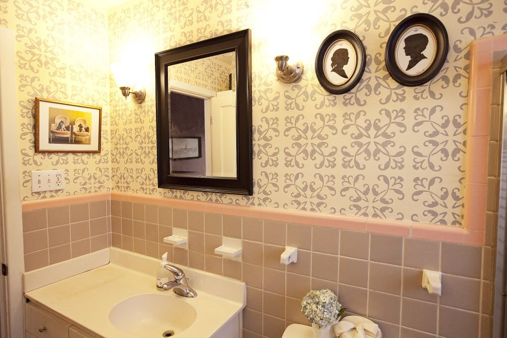 Lilly Neubauer used the original pink tilling in the bathroom as a jumping-off point. She stenciled the walls and accessorized with silhouettes, which she and her husband had made during their honeymoon, and poodle artwork to add to the vintage feel. 07132013xARTSLIFE