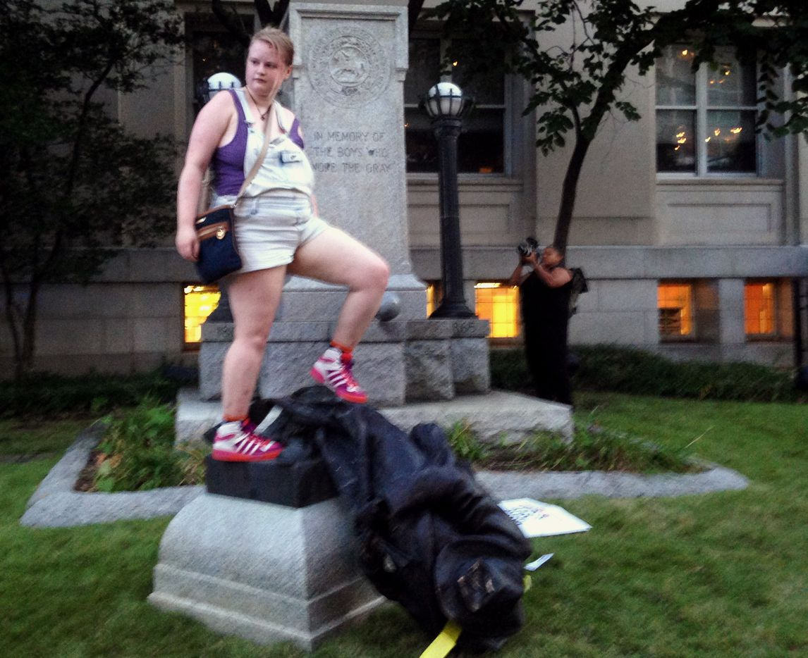 Claire Meddock, 21, stands on a toppled Confederate statue on Monday, Aug. 14, 2017, in Durham, N.C. Activists on Monday evening used a rope to pull down the monument outside a Durham courthouse. The Durham protest was in response to a white nationalist rally held in Charlottesville, Va, over the weekend. Authorities say one woman was killed Saturday after one of the white nationalists drove his car into a group of counterprotesters.