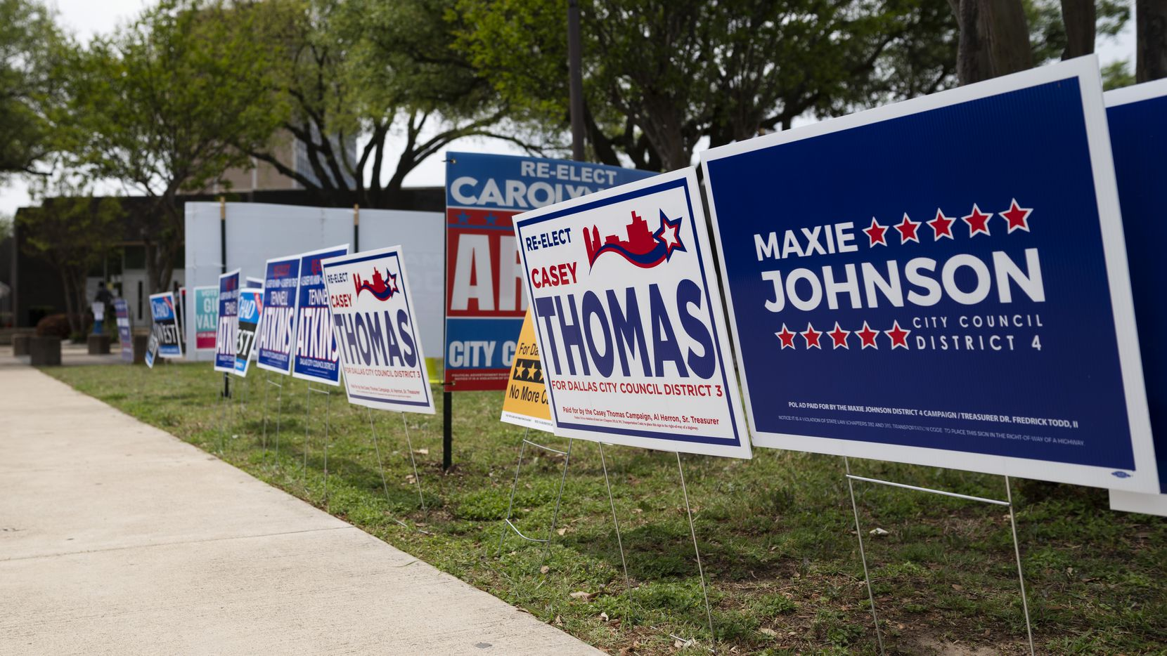 Campaign signs for Dallas City Council candidates fill the grass areas outside of the Oak Cliff Sub-Courthouse on the first day of early voting in Dallas, on Monday.