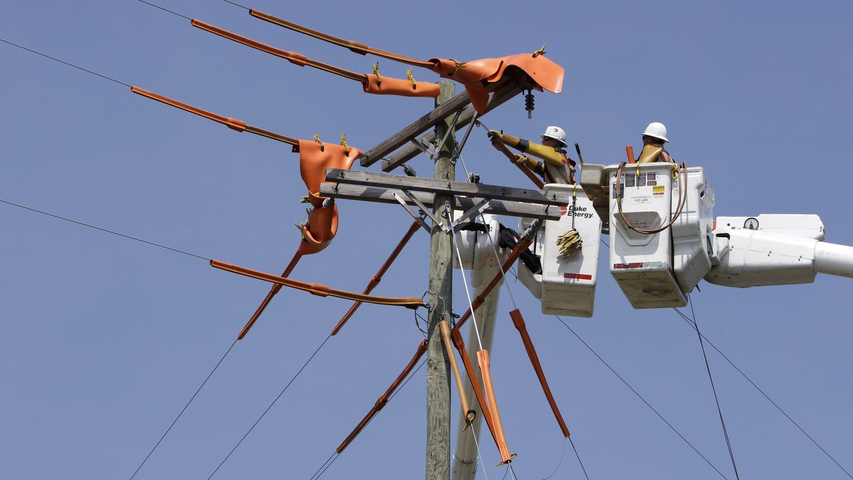 In this 2010 photo, Duke Energy linesmen work on power lines in Charlotte, N.C.