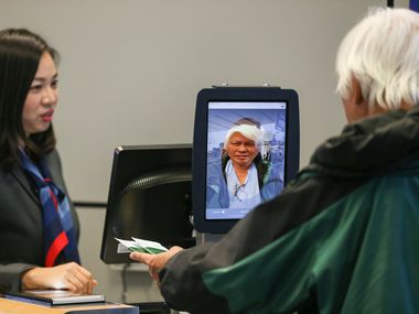 Gate agent Erica Shin assists as passengers board an American Airlines flight to Tokyo Narita International Airport using facial biometric scanning at DFW Airport's Terminal D.