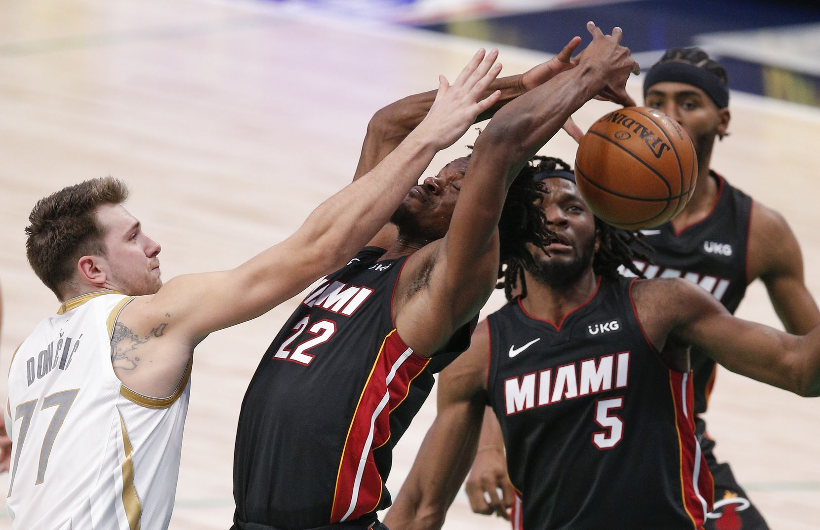Dallas Mavericks guard Luka Doncic (77) battles Miami Heat forwards Jimmy Butler (22) and Precious Achiuwa (5) for the ball during the first half of an NBA basketball game, Friday, January 1, 2021. (Brandon Wade/Special Contributor)