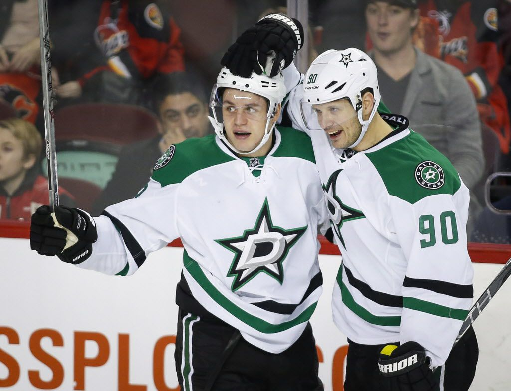 Dallas Stars' Mattias Janmark, left, of Sweden, celebrates his goal against the Calgary Flames with teammate Jason Spezza during the second period of an NHL hockey game in Calgary, Alberta, Tuesday, Dec. 1, 2015. (Jeff McIntosh/The Canadian Press via AP) MANDATORY CREDIT