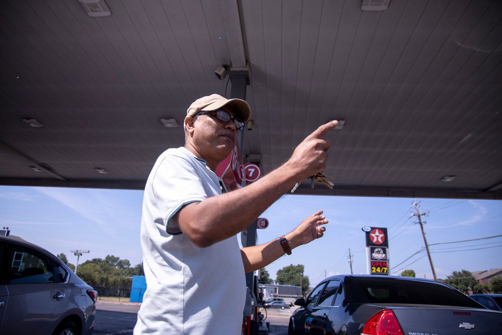 Store manager Abdullah Mahmood  points at a bullet hole on the roof of the Texaco he manages at Ferguson Road and Interstate 635. The city of Dallas is suing the store, claiming it's a hub for drug sales.