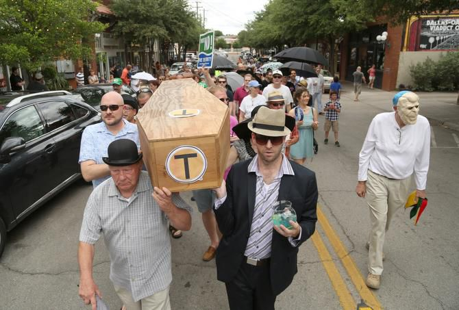 Pallbearers Ed Meyer (left) and Patrick Kennedy carried a fake coffin in the Bishop Arts District of Oak Cliff as part of a New Orleans-style funeral march for the Trinity River toll road project, which has an estimated price tag of $1.8 billion.