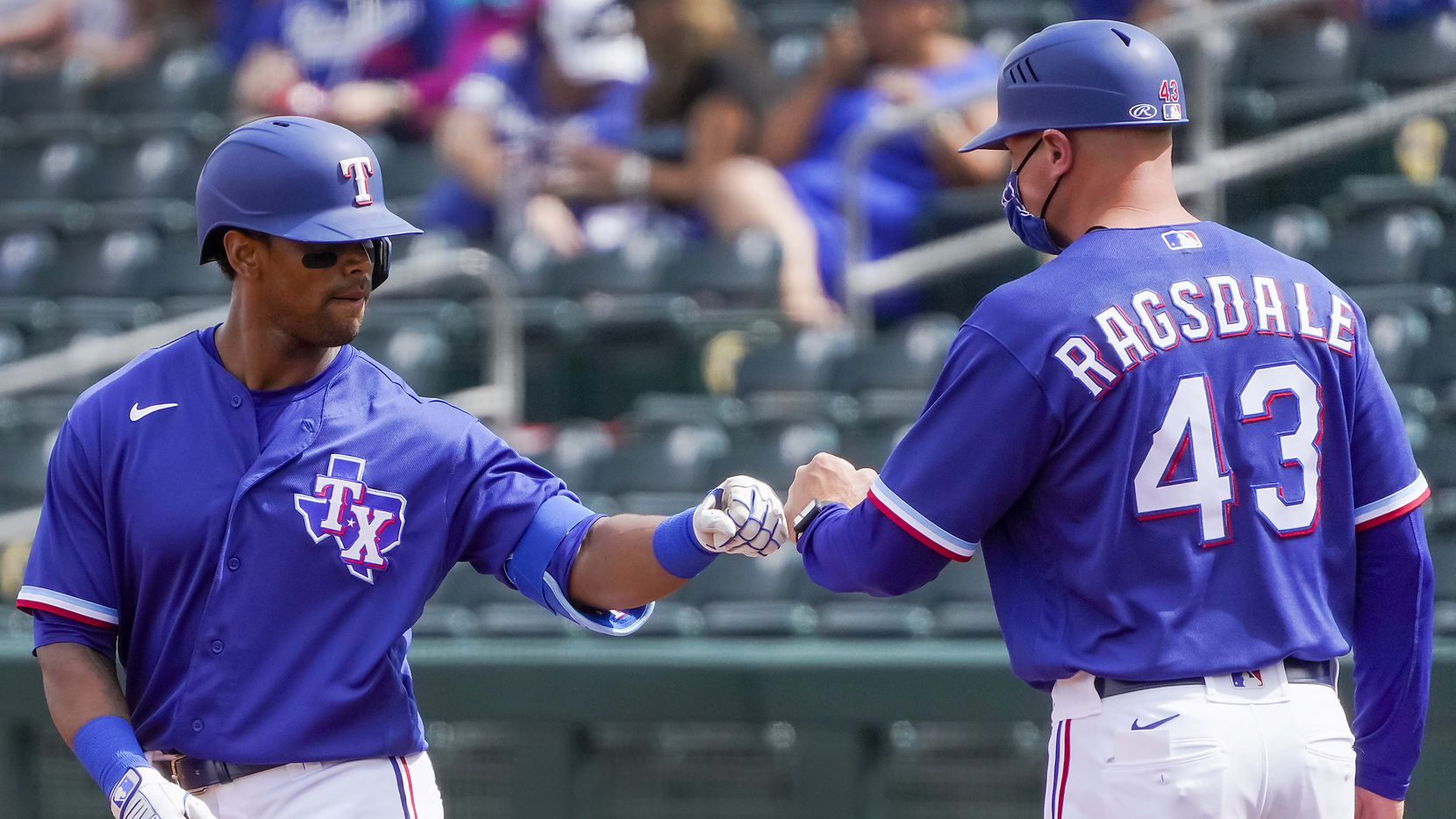 Texas Rangers designated hitter Khris Davis celebrates with  field coordinator/first base coach Corey Ragsdale after picking up his first hit of the spring with a single during the first inning of a spring training game against the Los Angeles Dodgers at Surprise Stadium on Sunday, March 7, 2021, in Surprise, Ariz. (Smiley N. Pool/The Dallas Morning News)