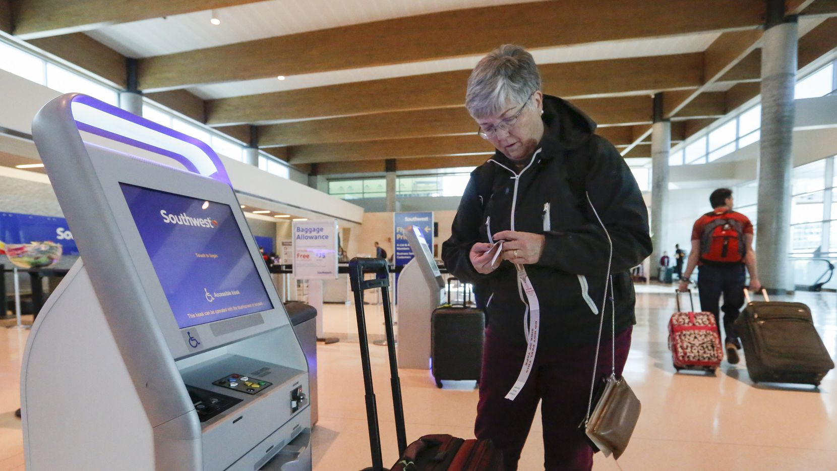 Ann Allen uses a Southwest Airlines kiosk to print some luggage tags at Dallas Love Field Wednesday, November 22, 2017. She was passing through Dallas from El Paso, Texas. (Ron Baselice/The Dallas Morning News)