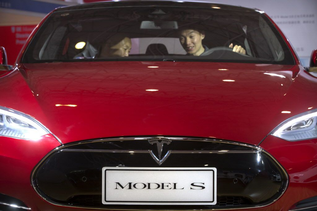 """In this Monday, April 25, 2016, file photo, a man sits behind the steering wheel of a Tesla Model S electric car on display at the Beijing International Automotive Exhibition in Beijing. Federal officials say the driver of a Tesla S sports car using the vehicle's """"autopilot"""" automated driving system has been killed in a collision with a truck May 7 in Williston, Fla., the first U.S. self-driving car fatality."""