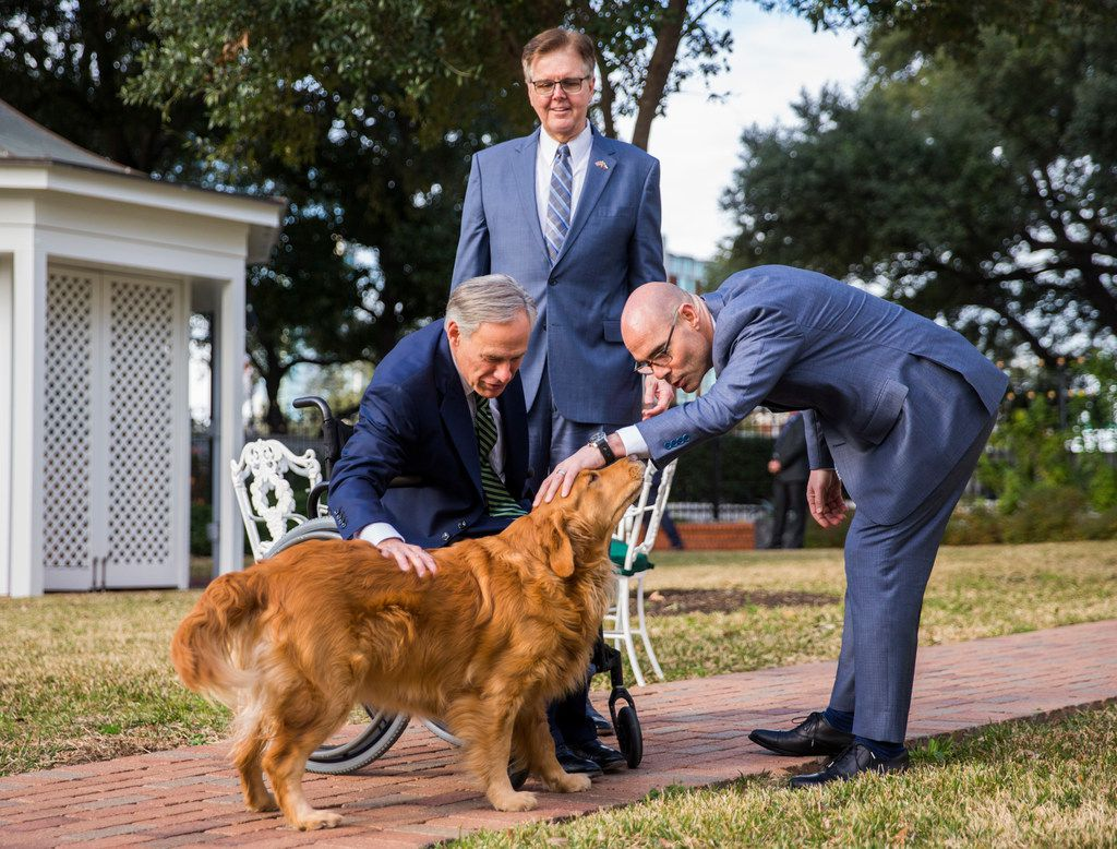 Governor Greg Abbott, Lt. Governor Dan Patrick and Speaker of the House Dennis Bonnen pet one of the governor's dogs, Pancake, in the yard after a press conference at the Governor's mansion on the second day of the 86th Texas legislature on Wednesday, January 9, 2019 in Austin, Texas.
