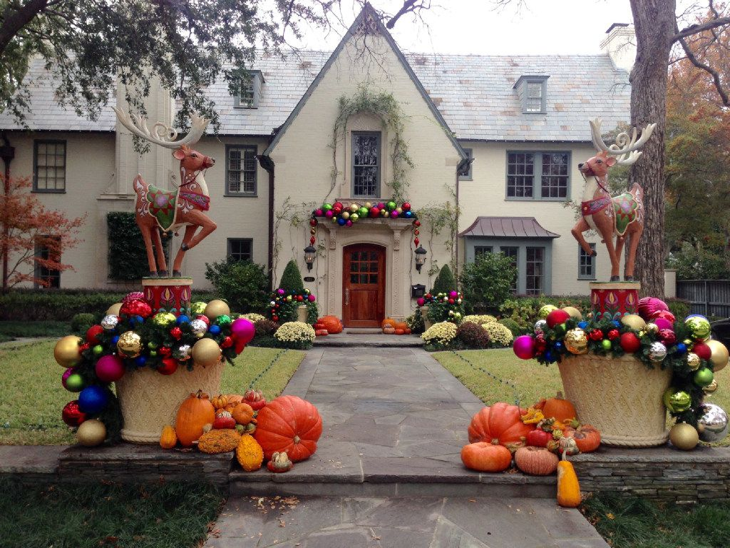 A mix of colorful, oversized ornaments spill over the sides of two large planters and embellish a doorway mantel.