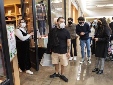 A mask shopper, not identified by name, is temporarily turned away from the retail store J. Crew by sale associate Jackie Moreno, far-left, due to the store's reaching limited capacity part of their COVID-19 restrictions at NorthPark Center in Dallas, on Friday, Nov. 27, 2020.