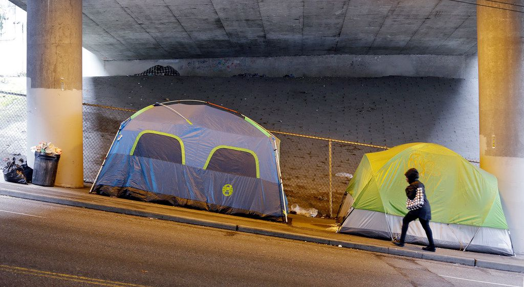 In this 2017 file photo, a person walks up a hill next to tents lined up beneath a highway close to downtown Seattle.