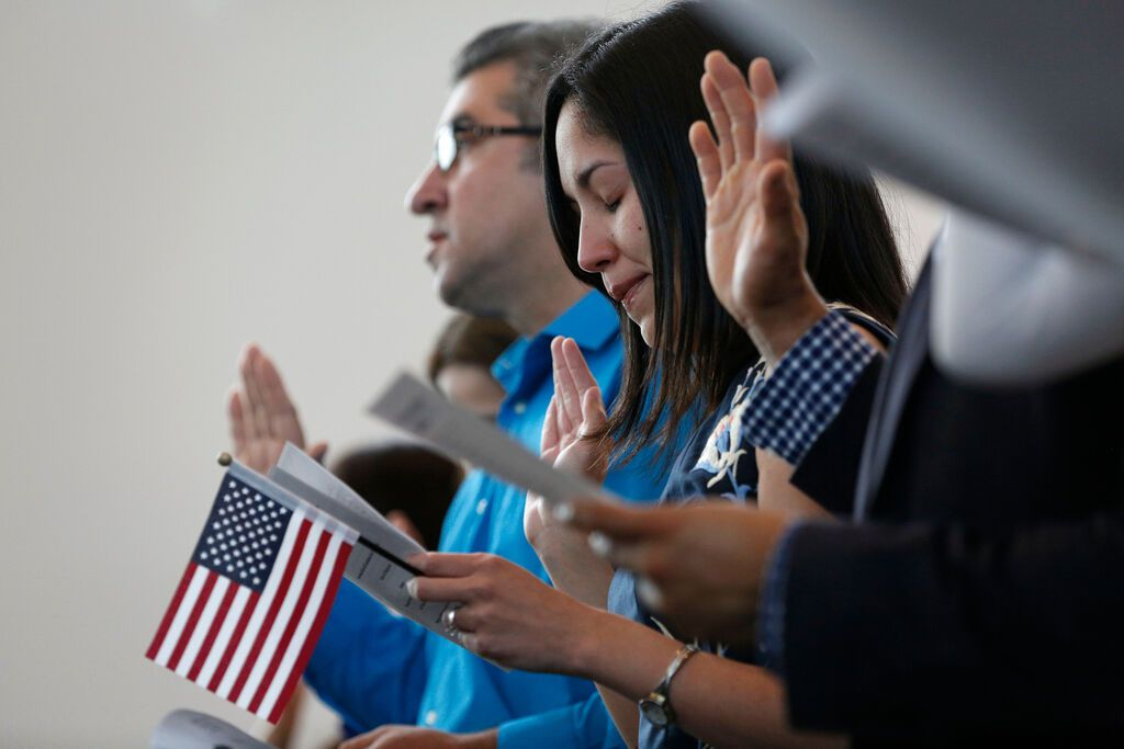 Julieta Chiquillo takes the Oath of Allegiance for her U.S. citizenship at the U.S. Citizenship and Immigration Services in Irving, Texas on April 21, 2016. (Rose Baca/The Dallas Morning News)