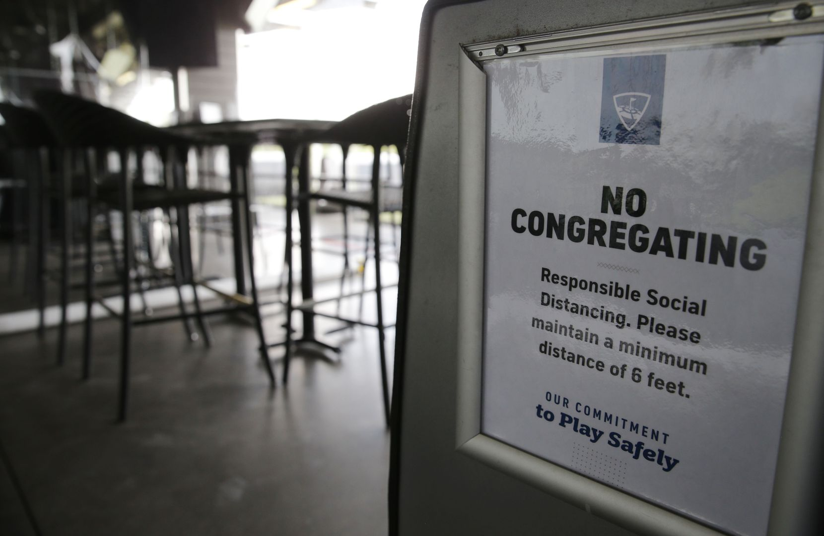 A sign is displayed encouraging social distancing at Topgolf in The Colony, on Friday, May 22, 2020.