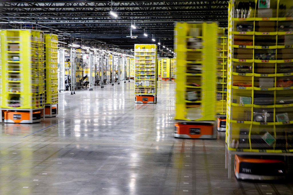 Robots carrying tall pods loaded with Amazon products move packages throughout an Amazon fulfillment center in Coppell.
