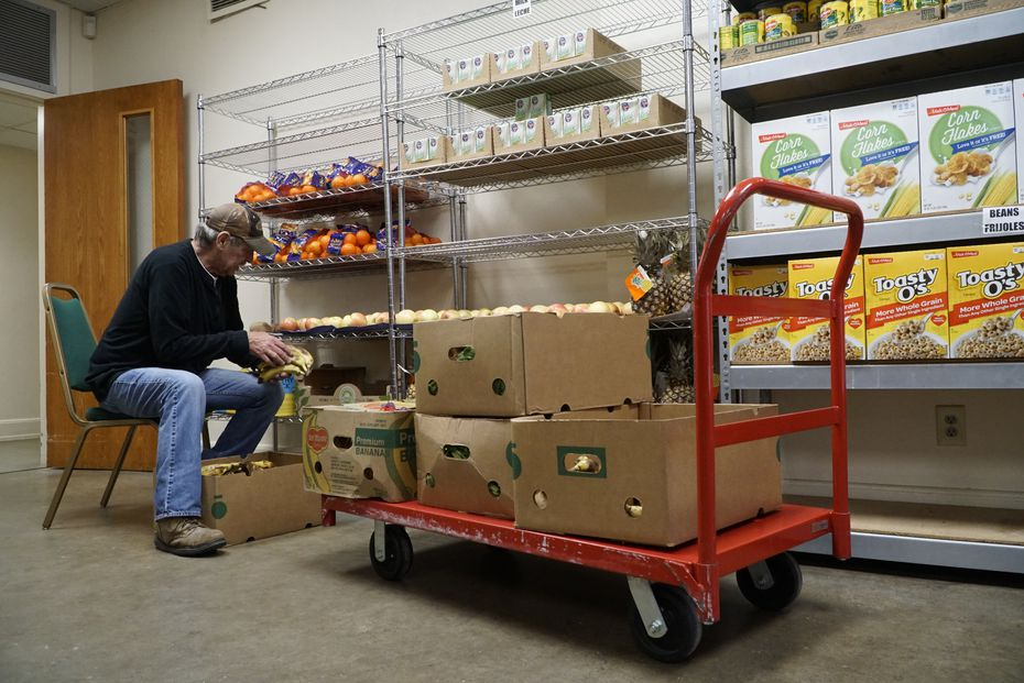 Mark Blaker stocks the food pantry at Mission Oak Cliff in Dallas on Tuesday,  Dec. 10, 2019.