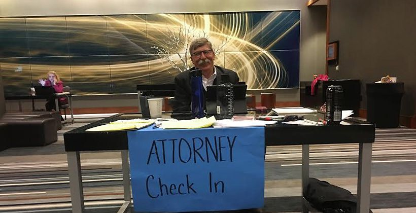"Bill Holston, executive director of the Human Rights Initiative of North Texas, mans the check in table outside the ""war room"" for attorneys volunteering to help detainees at D-FW International Airport Sunday."