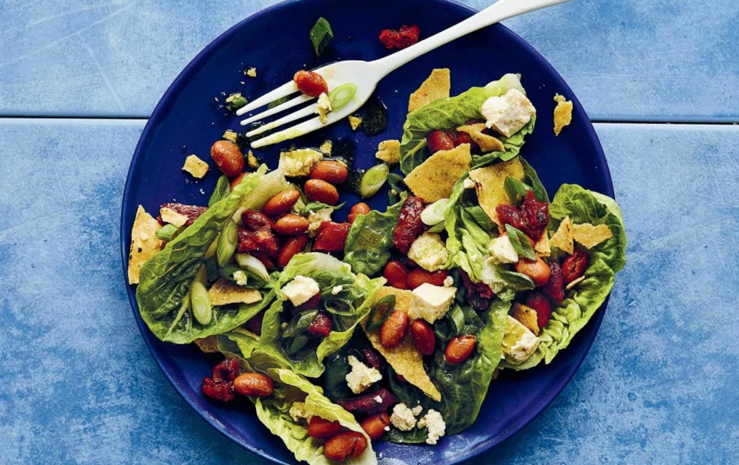 La Texas Salad tiene una base de totopos y frijoles.