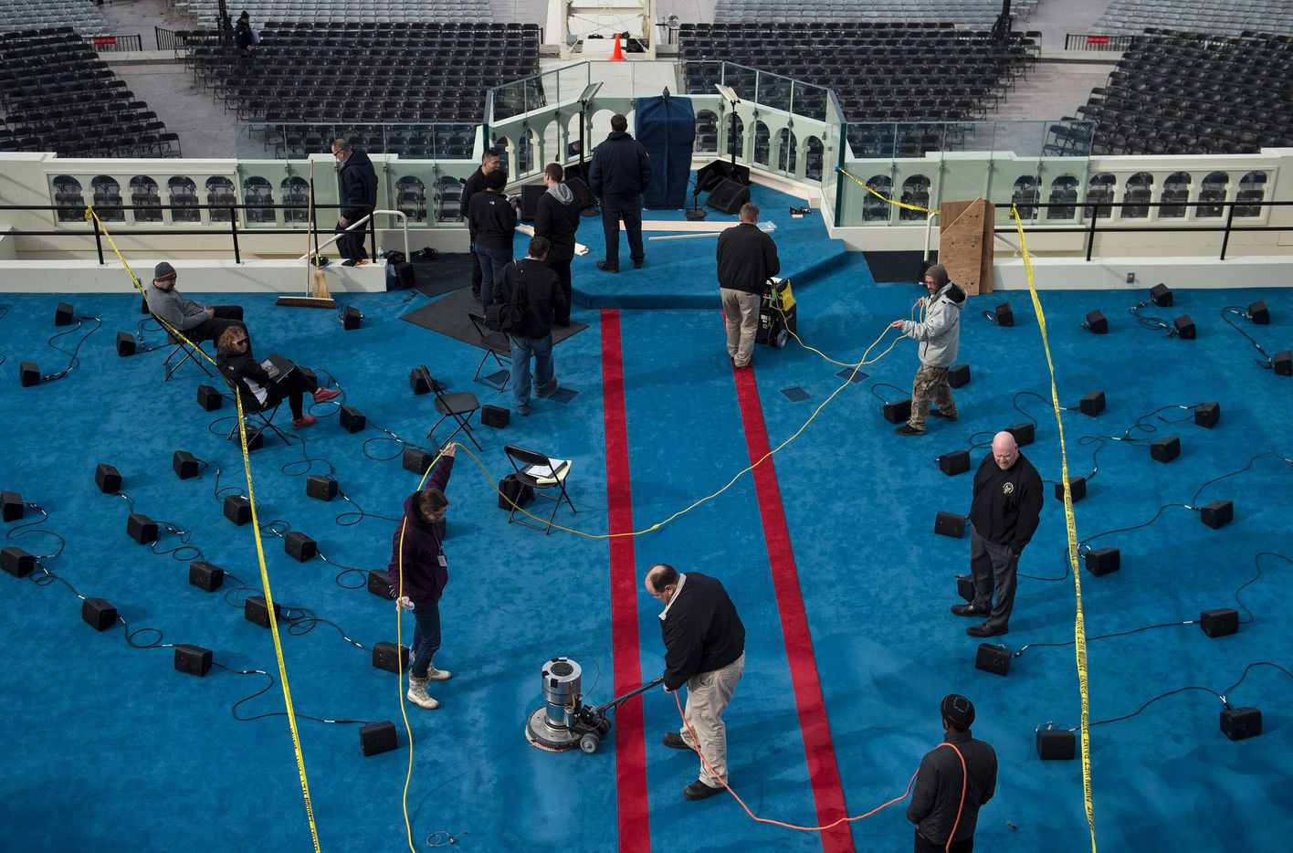Workers clean the carpet on the Inauguration platform in preparation for tomorrow's Inauguration on Capitol Hill on January 19, 2017 in Washington, DC. With one day to go before he takes the oath of office as the 45th US president, Donald Trump arrives in Washington Thursday determined to transform US politics over the next four years.