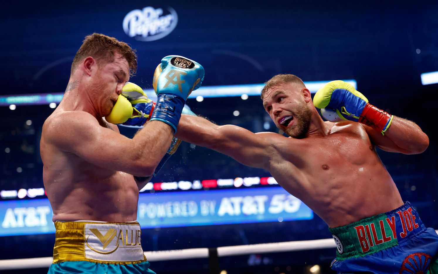 Boxer Billy Joe Saunders (right) gets a clean shot to the face of Canelo Alvarez during their unified super middleweight title fight at AT&T Stadium in Arlington, Saturday, May 8, 2021. Saunders couldn't go on to the ninth round because he sustained an eye injury and could not see. (Tom Fox/The Dallas Morning News)