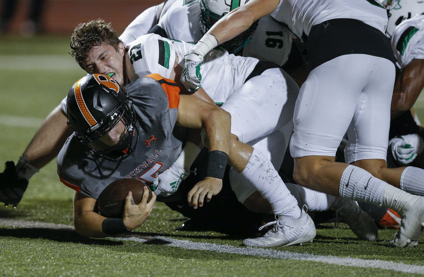 Rockwall sophomore quarterback Lake Bennett (5) scores a touchdown as Southlake Carroll senior defensive back Mason Grawe (27) defends during the first half of a high school football game at Wilkerson-Sanders Stadium in Rockwall, Thursday, October 8, 2020. (Brandon Wade/Special Contributor)