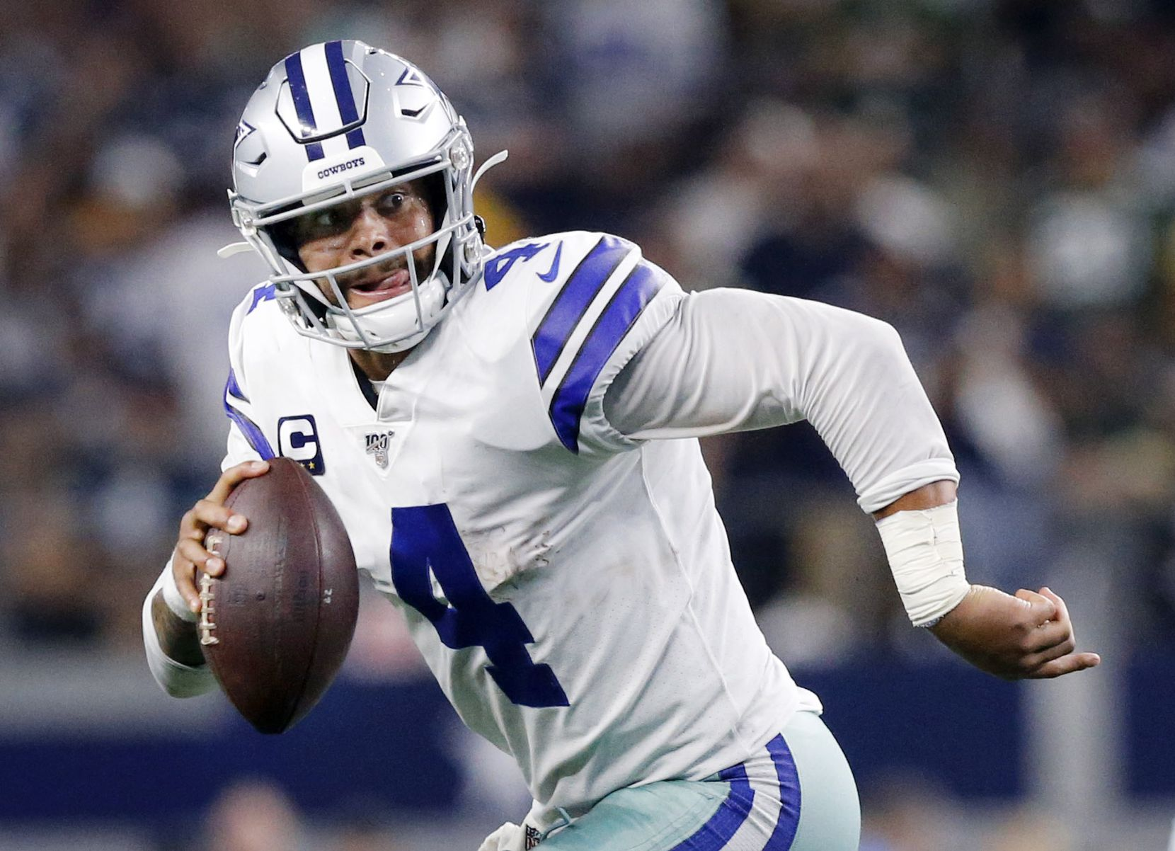 FILE - Cowboys quarterback Dak Prescott (4) rolls out for a pass during the fourth quarter of a game against the Packers at AT&T Stadium in Arlington on Sunday, Oct. 6, 2019.