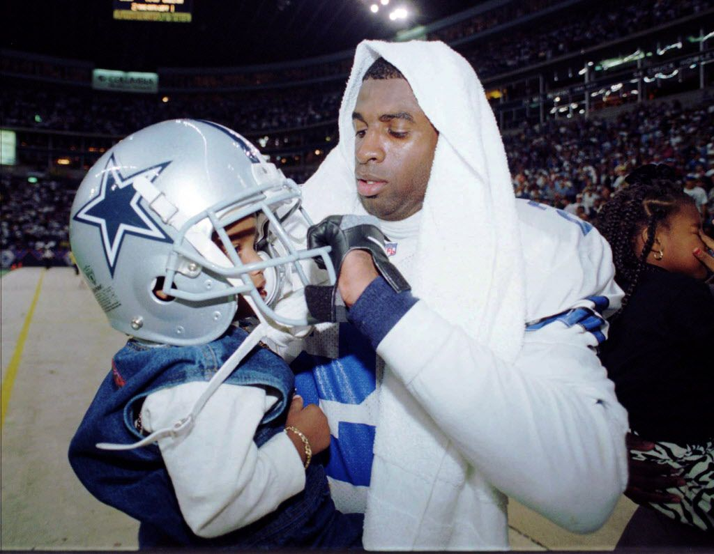 Dallas Cowboys' Deion Sanders, right, places his helmet on his son Deion Sanders, Jr. after the Cowboys beat the Green Bay Packers 38-27 in the NFC title game Sunday, Jan. 14, 1996, in Irving, Texas. Sanders will play in his second straight Super Bowl. He played with the San Francisco 49ers last year. (AP Photo/Tim Sharp)