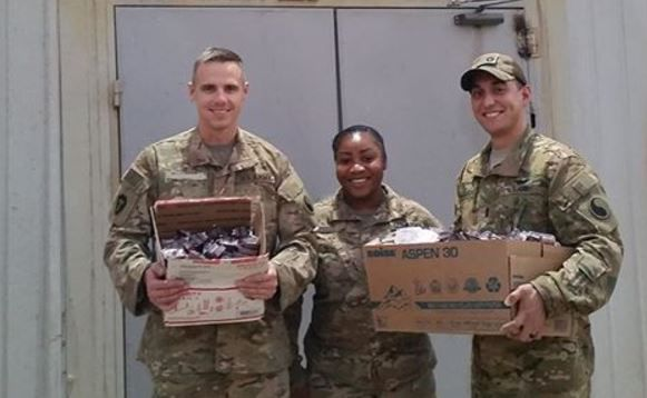 U.S. Army 1st Lt. Jessie Guajardo, right, and two other service personnel have their hands full of Chick-fil-A condiment packets.