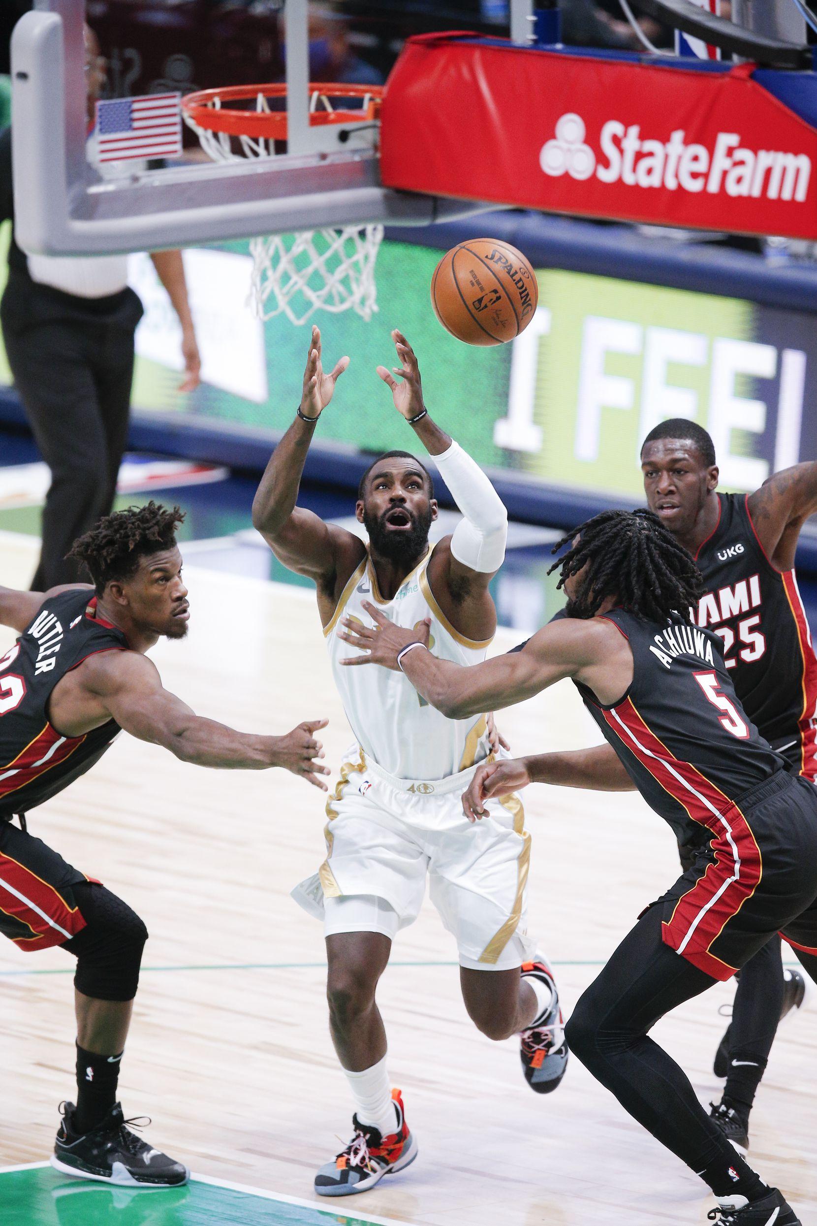 Dallas Mavericks guard Tim Hardaway Jr. (11) loses his grip on the ball as Miami Heat forwards Jimmy Butler, left, Precious Achiuwa (5) and guard Kendrick Nunn (25) defend  during the first half of an NBA basketball game, Friday, January 1, 2021. (Brandon Wade/Special Contributor)