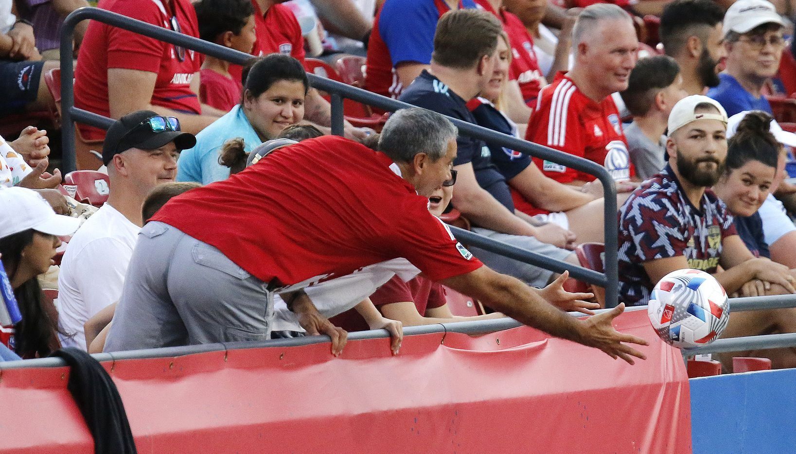 A fan attempts to snag a stray kick during the first half as FC Dallas hosted Sporting Kansas City at Toyota Stadium in Frisco on Saturday evening, August 14, 2021. (Stewart F. House/Special Contributor)