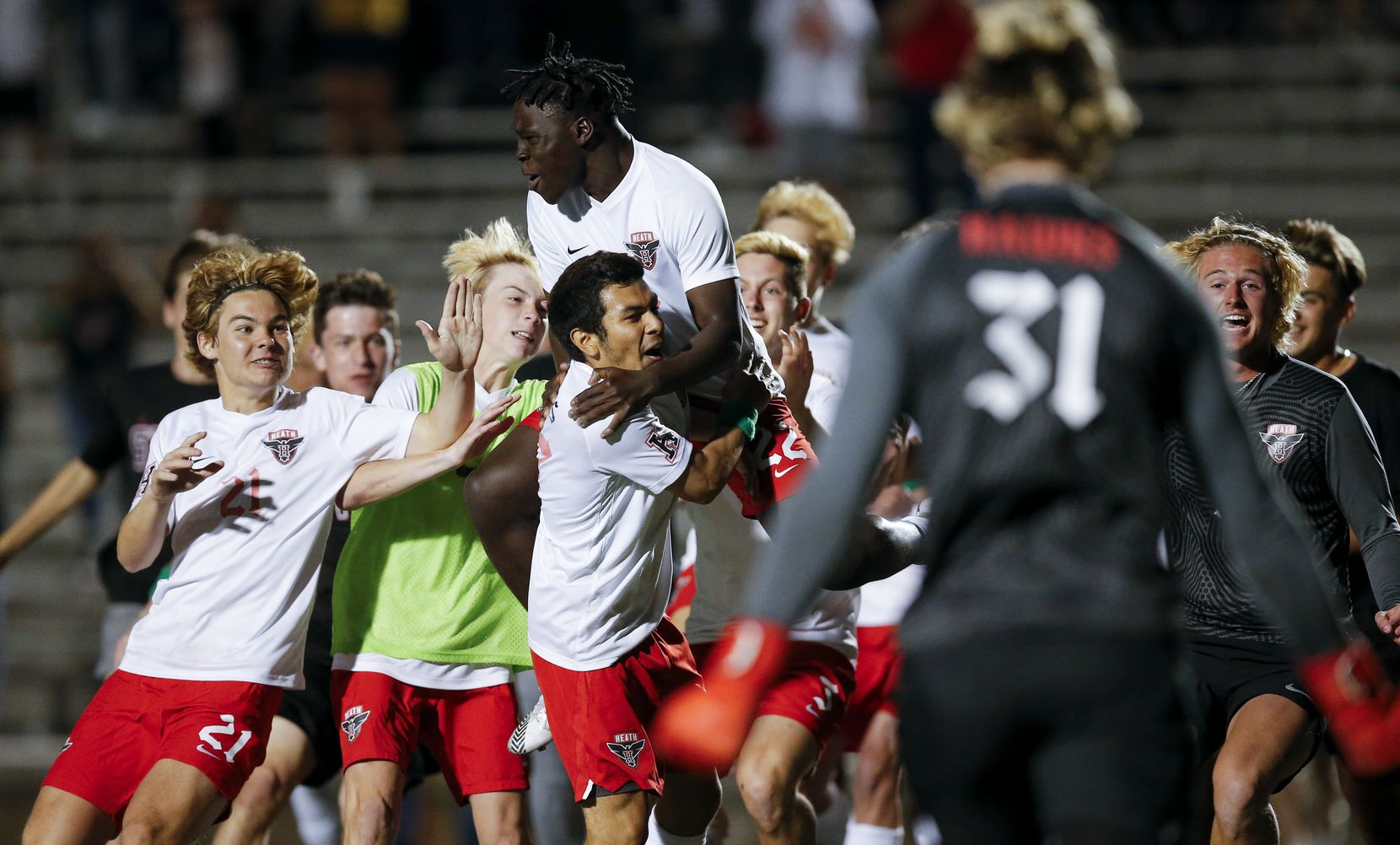 Rockwall-Heath senior defender Oscar Perales, center, is mobbed by teammates after scoring the game winning goal in a shootout after a boys soccer Class 6A state semifinal against Allen at Mesquite Memorial Stadium in Mesquite, Tuesday, April 13, 2021. Rockwall-Heath won 3-1 in a shootout. (Brandon Wade/Special Contributor)