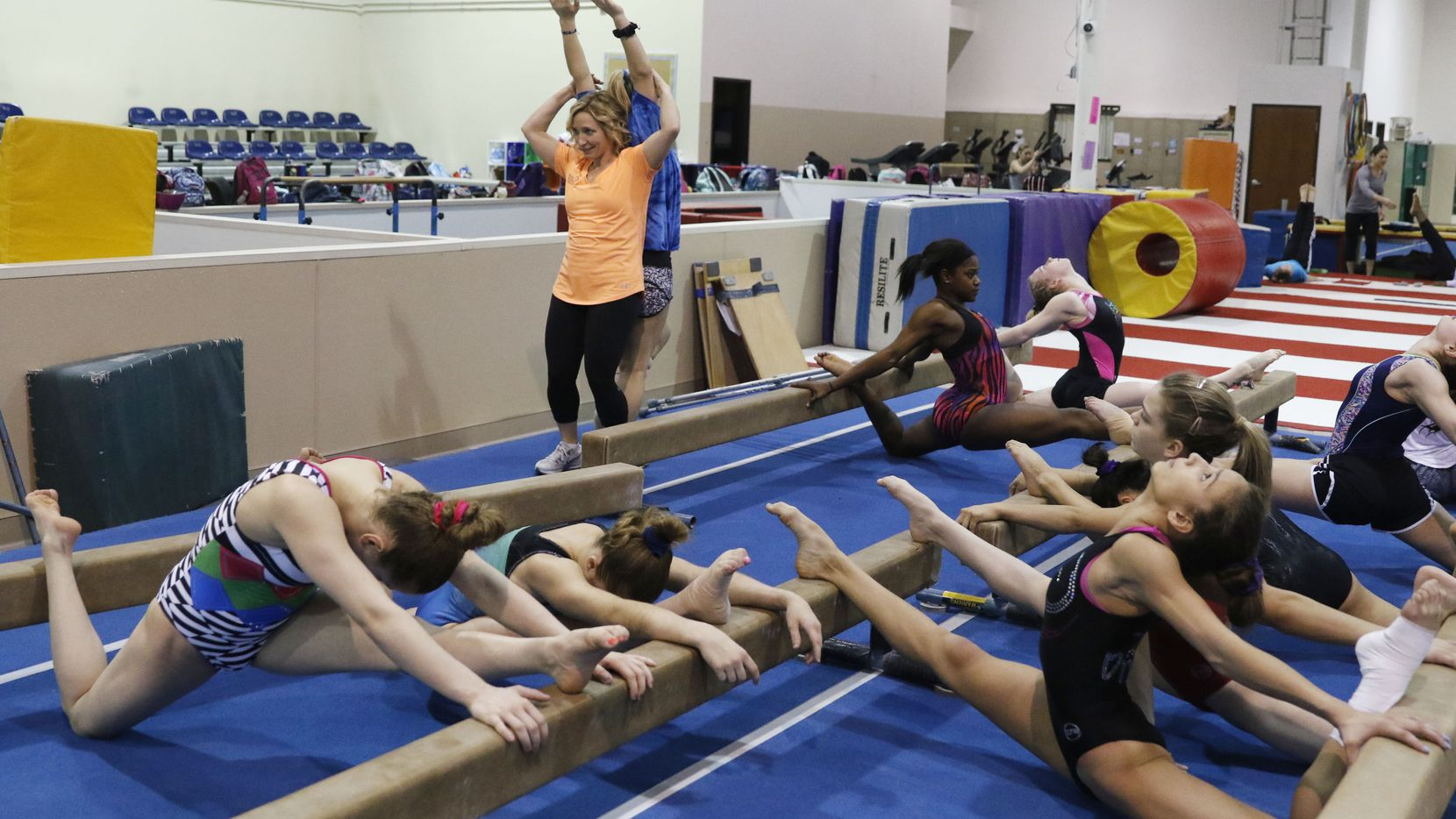 Kim Zmeskal, right, retired artistic gymnast, who was a national champion, world champion, and an Olympic bronze medalist helps one of her gymnast stretch her back at the Texas Dreams Gymnastics in Coppell, Texas, Wednesday, Feb. 28, 2018. (David Woo/The Dallas Morning News)