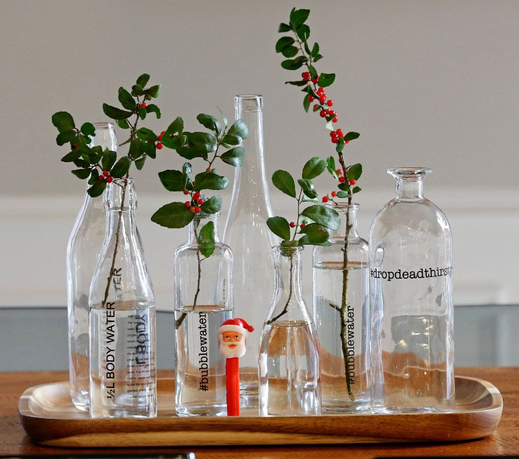 A grouping of glass bottles gets a holiday look with a  a few snippings from the yard. Putting the bottles on a tray unifies the look.
