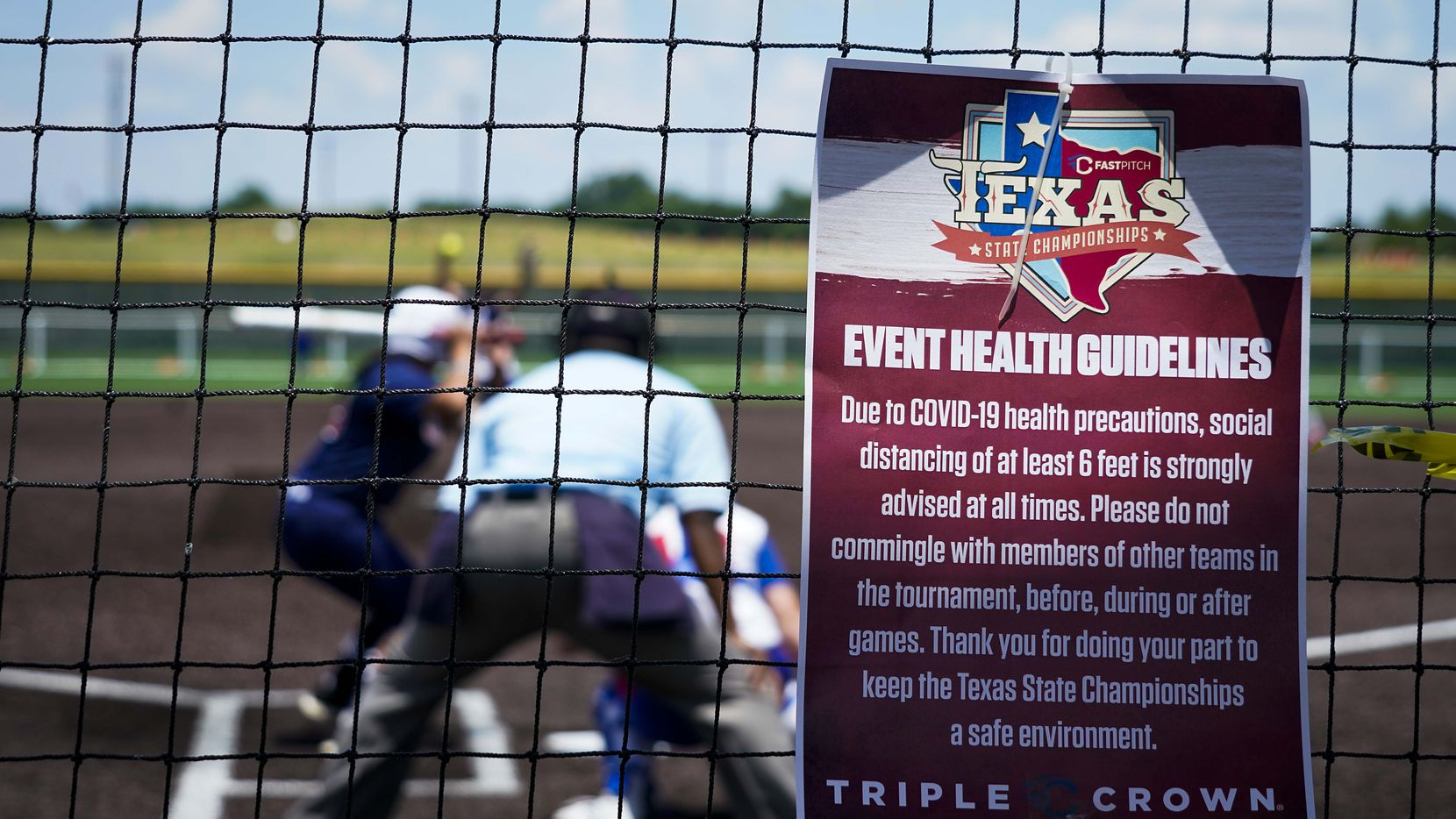 A sign encouraging social distancing, and discourage commingling of teams, hangs on the backstop during a game between the Texas Glory 18U team (in white jerseys) and the American Freedom Gold Coleman 18U in the Triple Crown Texas State Tournament at Spirit Park on Monday, June 15, 2020, in Allen, Texas.