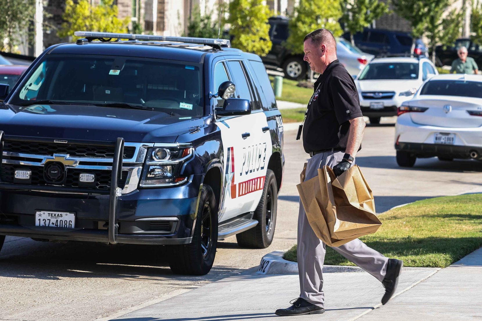 An Arlington police officer carries bags of evidence from Timothy George Simpkins' home.