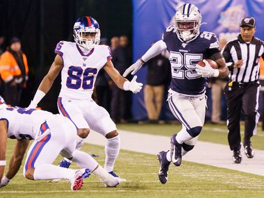 Dallas Cowboys free safety Xavier Woods (25) returns an interception on a pass intended for New York Giants wide receiver Darius Slayton (86) during the first half of an NFL football game, Monday, Nov. 4, 2019, in East Rutherford, N.J.