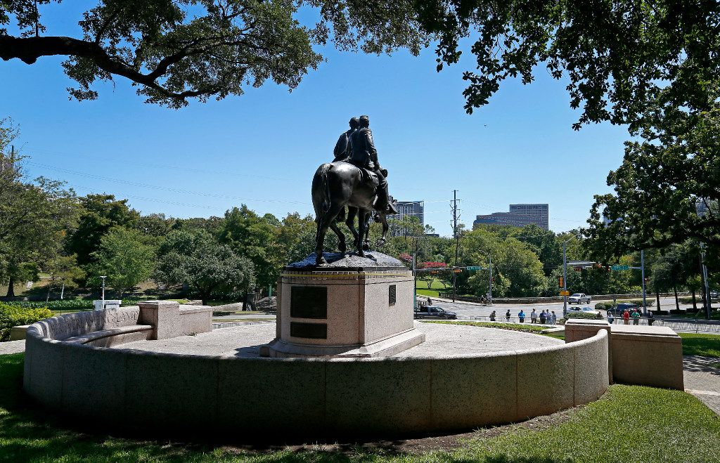 People watch the statue of Robert E. Lee, which is fenced off at Robert E. Lee Park in Dallas, Thursday, Sept. 7, 2017. The Dallas City Council had voted in favor of immediate removal and crews had been trying to figure out how to remove the statue through much of the afternoon until the process was halted by a temporary restraining order from U.S. District Judge Sidney A. Fitzwater.