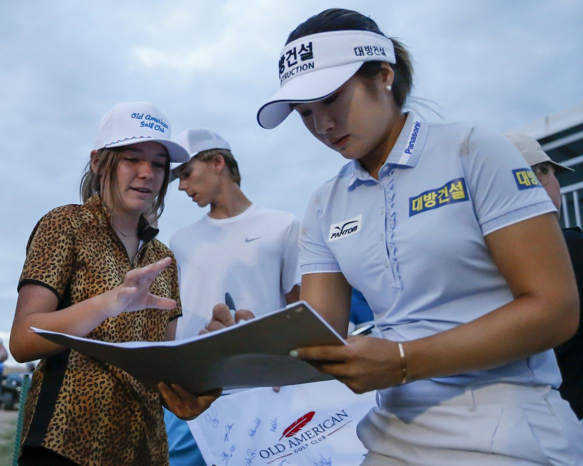 Professional golfer Jeongeun Lee6 (right) signs a pin flag for Emma Darnold, 14, of Andrews, Texas after the third round of the LPGA VOA Classic on Saturday, July 3, 2021, in The Colony, Texas. (Elias Valverde II/The Dallas Morning News)