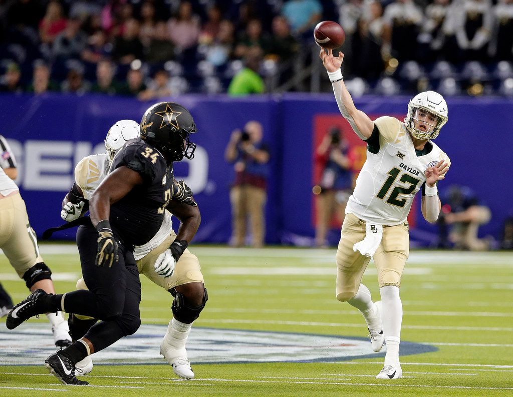 Baylor quarterback Charlie Brewer (12) passes the ball as Vanderbilt defensive lineman Dare Odeyingbo (34) closes in during the first half of the Texas Bowl NCAA college football game, Thursday, Dec. 27, 2018, in Houston. (AP Photo/Michael Wyke)