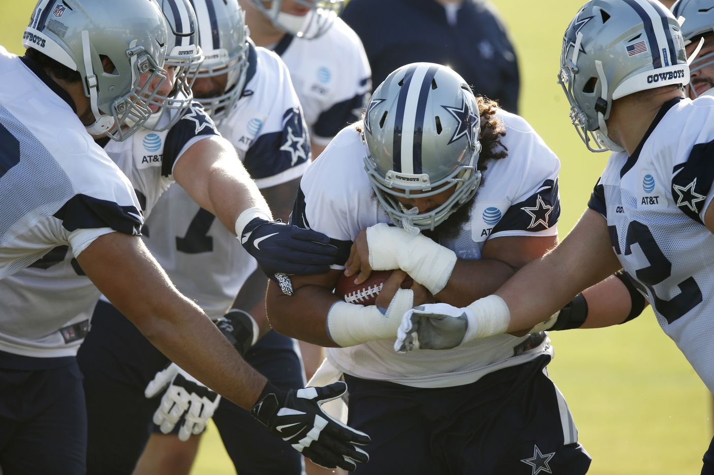 Dallas Cowboys center Joe Looney (73) holds the ball tightly as he runs through a gauntlet of players swiping at the ball during the first day of training camp at Dallas Cowboys headquarters at The Star in Frisco, Texas on Friday, August 14, 2020. (Vernon Bryant/The Dallas Morning News)